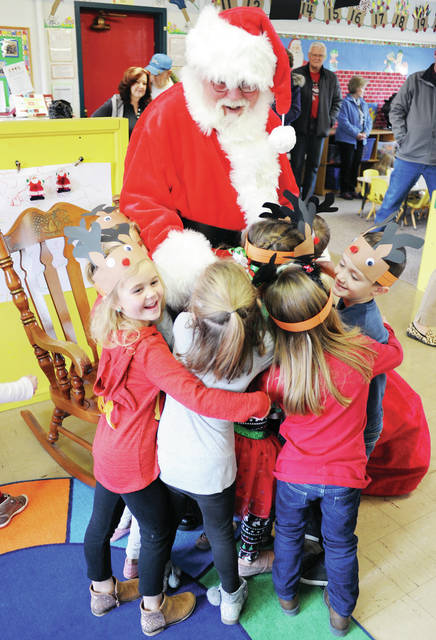 Santa is swarmed by children for a group hug as he stands up to leave the Co-Op Nursery School on Thursday, Dec. 12. Kids took turns sitting on Santa's lap and having their pictures taken by their parents. The students then sang Santa songs.