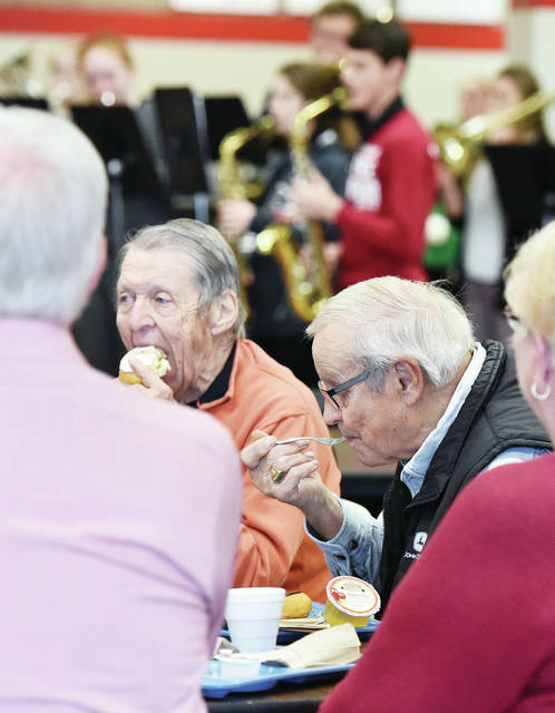 Ed Lachey, left, bites into a donut and Don Puthoff, both of Minster, eats at the annual Senior Citizens Breakfast at Fort Loramie High School on Thursday, Dec. 12. Fort Loramie High School band members performed during the meal. The meal was free to members of the Fort Loramie community.