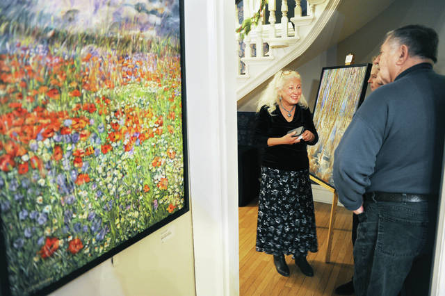Elena Filshtinska-Burwell, of Columbus, left, talks with Joann Scott and Chuck Coy, both of Sidney, during opening night of her art exhibit at the Gateway Arts Council on Friday, Dec. 13. The show consists of oil, acrylic and watercolor paintings done in different Russian styles of painting. Filshtinska-Burwell was born in Siberia and raised in Kharkov, Ukraine. The show will run through Friday, January 31, 2020.