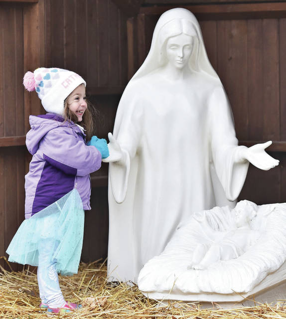 Catherine Mendes, 2, of Minster, daughter of Maria and Joel Mendes, shakes the hand of Mary in a Nativity located near the Minster Gazebo where Santa was taking requests on Saturday, Dec. 14.