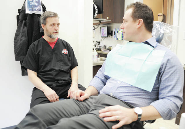 Dr. Ben Warnock, left, of Harrod, talks with patient and Western Ohio Mortgage employee Adam Rose, of DeGraff, at Evers Dental Center recently. Warnock purchased the practice from Dr. Matthew Evers.