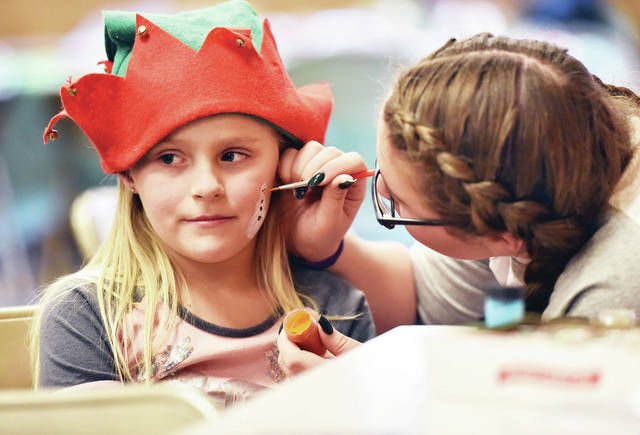 Chaynee Turner, left, 7, of Sidney, daughter of Leann and Koltte Grile, has a snowman painted on her cheek by Brianna Cardinal, 15, of Troy, daughter of Erica Bill and Brian Cardinal, at the New Life Church Christmas party held in the Port Jefferson Community Hall on Saturday, Dec. 14. The party included a Bible reading of the Christmas story, songs, food and games.