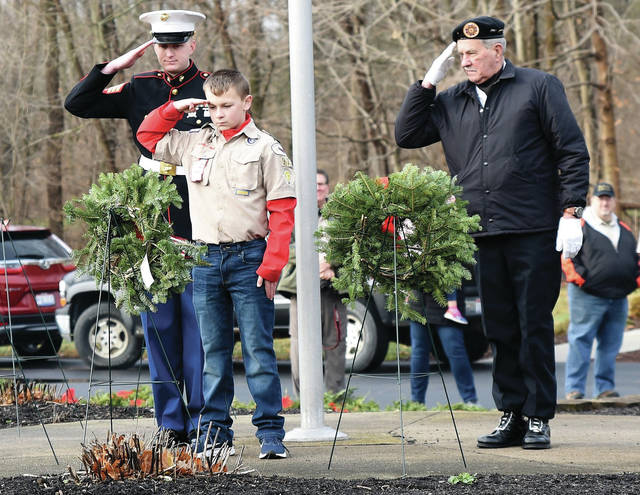 Sgt. Nathan Shultz, USMC, left to right, Dylan Shaffer,12, of Houston and Bill Carpenter, of Sidney, lay a wreath at the base of the flag pole at Graceland Cemetery on Saturday, Dec. 14. The three were taking part in a Wreaths Across America program that the Shelby County Historical Society and the Shelby County Vets to DC teamed up to hold the event. Wreaths were place on the graves of hundreds of U.S. veterans at Graceland Cemetery.