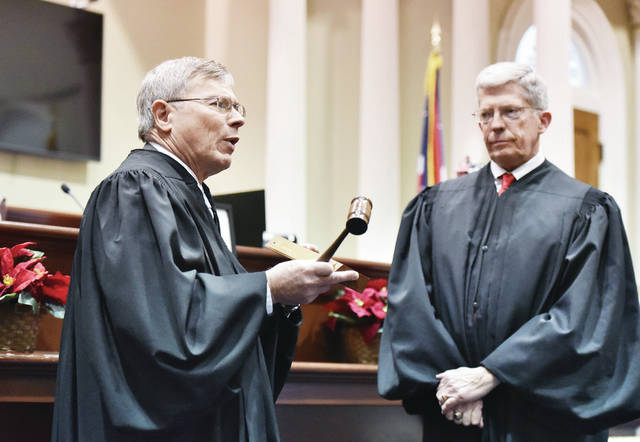 Shelby County Common Pleas Judge James F. Stevenson, left, presents Shelby County Municipal Court Judge Gary Carter with a gavel and plaque that are passed down to each new judge. The plaque has the names of past judges and their years served etched on it. Stevenson presented the items after swearing Carter in as the new Shelby County Municipal Court Judge on Friday, Dec. 27.