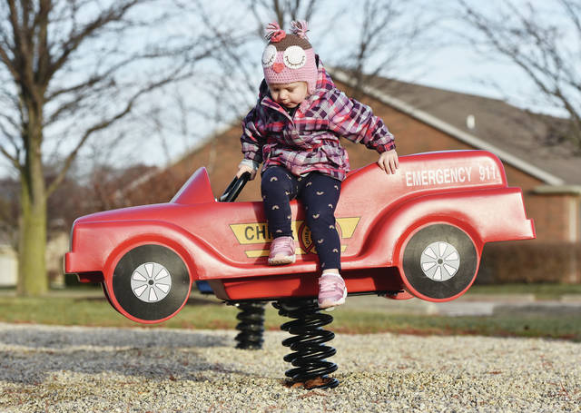 Hazel Spenceley, 2, of Brooklyn, N.Y., daughter of Paul and Kim Spenceley, hops out of spring mounted toy car at Plum Ridge Park on Thursday, Dec. 27. Hazel was in town visiting her grandpa, John Boedighelmer, for Christmas.