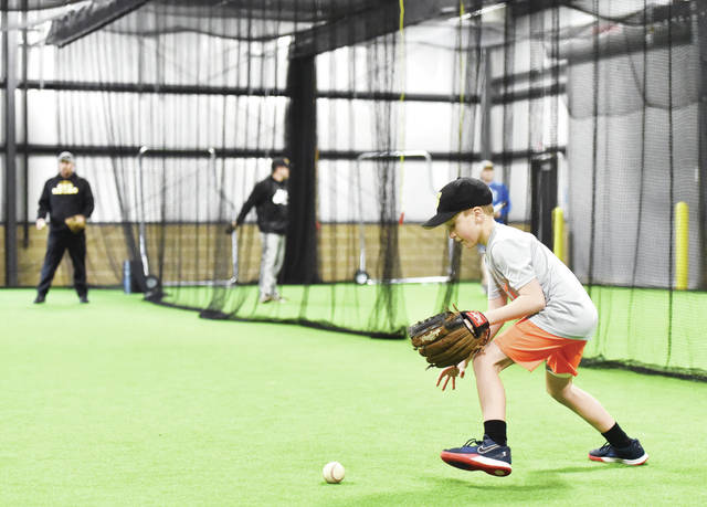 Emmett VanTilburgh, 7, of Sidney, son of Jenn and Chris VanTilburgh, goes after a ball that was hit to him during a youth baseball camp held in the new Goffena Training Facility on Friday, Dec. 27. The Goffena Training Facility is located next to Sidney Memorial Stadium.