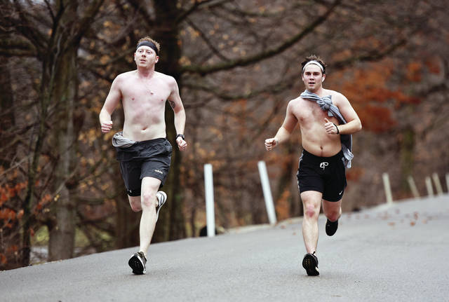 """Jim Marsh, left, and Ben McClain, both of Sidney, had to take off their shirts when they started to overheat during a run at Tawawa Park on Sunday, Dec. 29. McClain said they were motivated to run because """"The rain took a pause an it's a beautiful day."""""""