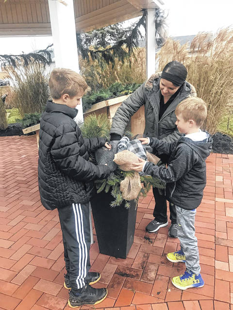 Botkins Beautification Club member Kimi Symonds puts finishing touches on Christmas decorations at Veteran's Park with the help of her sons, Dylan and Ethan Symonds.