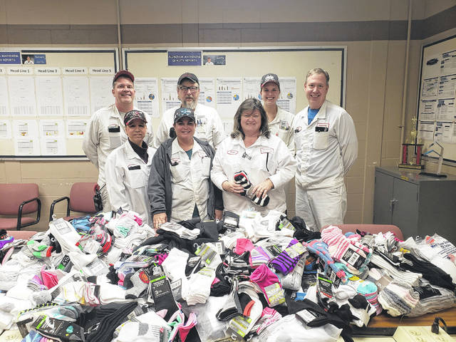 Honda of America's Anna Engine Plant associates collected more than 1,000 pairs of socks during a sock drive. Shown with the socks are, front row, left to right, Karen Orr, Tanya Campbell , Angie Zelaski, and back row, Dave Buxton, Don Keever, Kialee Koch and Rob Cordonnier.