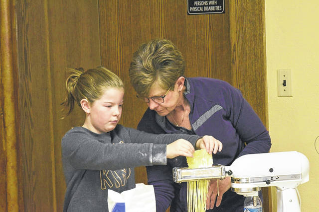 Nine-year-old Claire Albert, daughter of Rachel and Ben Albert, works with her grandmother, Sue Becher, as they cut noodles for the New Knoxville United Methodist Church's annual Christmas Bake Sale Extravaganza, which is Saturday, Dec. 7.