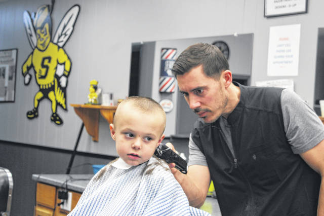 Aiden Place, 5, son of Danielle Purdy and Elizabeth Christman, of Sidney, gets his hair trimmed by Andy Steenrod at Downtown Barber Shop, 113 E. Court St., Sidney. Downtown Barber Shop is Aiden's favorite place to get his hair cut and he has been a loyal customer for years.