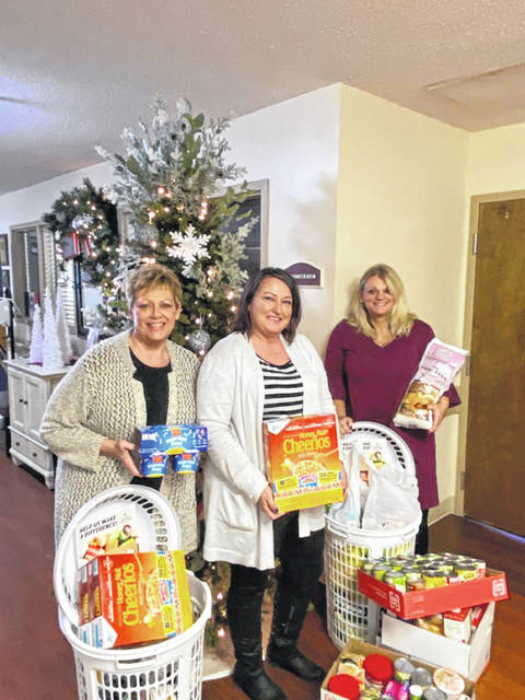 Chris Huber, nurse case manager, left to right, Kristy Earick, administrator, and Faith Young, admissions coordinator, show the items collected which were donated to the Versailles Council of Churches.