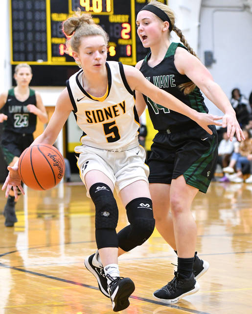Sidney junior guard Kelsey Kizer dribbles by Greenville's Morgan Gilbert during the first half a Miami Valley League game on Wednesday in Sidney. Kizer led the Yellow Jackets with 13 points.