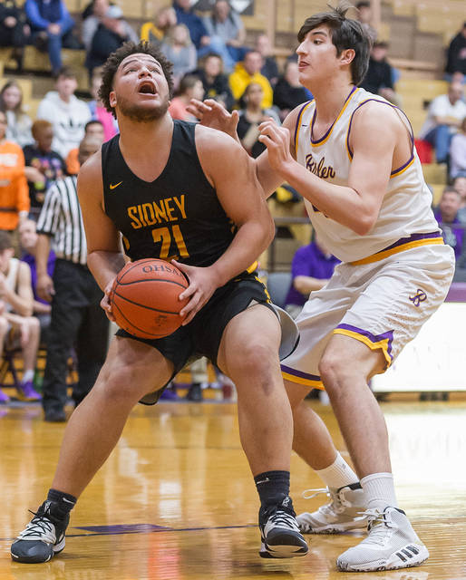 Sidney sophomore forward Jaden Swiger looks to shoot with pressure from Butler's Connor Buchanan during the first half of a Miami Valley League game on Tuesday in Vandalia. Swiger scored 10 points, eight of which came in the first half.