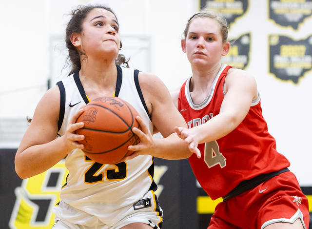 Sidney freshman guard Allie Stockton shoots with pressure from Troy's Laura Borchers during a Miami Valley League game on Wednesday in Sidney. Stockton led the Yellow Jackets with 15 points.