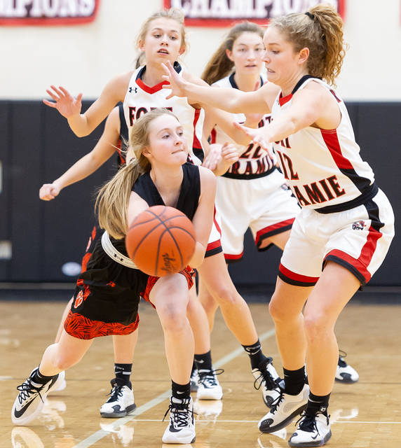 Jackson Center's Gwen Prenger, left, tries to pass while being guarded by Fort Loramie's Caitlyn Gasson, top left, and Kennedi Gephart, right, during the second half of a Shelby County Athletic League game on Thursday in Fort Loramie. The Redskins are holding opponents to an average of 21.1 points per game and have allowed more than 28 points once.