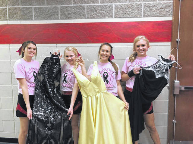 Fort Loramie Varsity Cheerleaders Hailey Wolfe, Iris Ruhenkamp, Emily Holthaus, and Kate Barhorst are shown with some of the gowns available at Sunday's prom dress exchange.