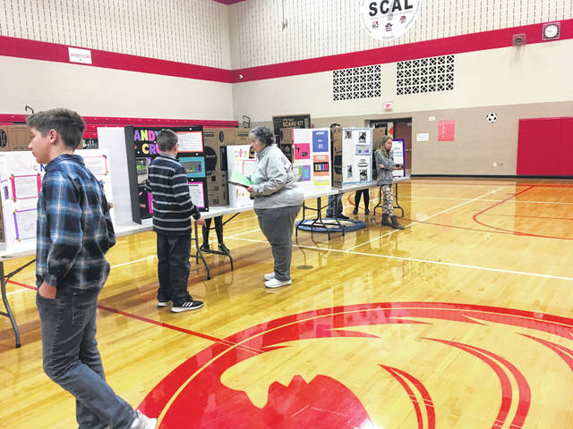 Judges look at the entries in the Houston Elementary School fourth-grade science fair.