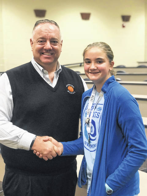 Minster Geography Bee Champion Lexi Hanson shakes Minster Social Studies teacher Mike Wiss' hand.