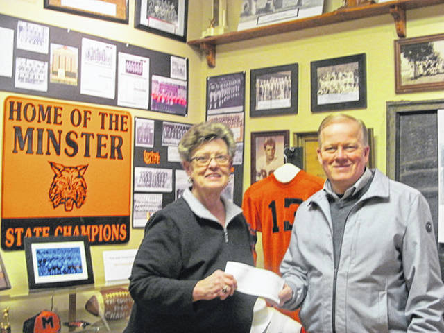 Mary Oldiges, of the Minster Historical Society, accepts a donation from Todd Weigandt, representing Area Electric and Weigandt Real Estate and Development.