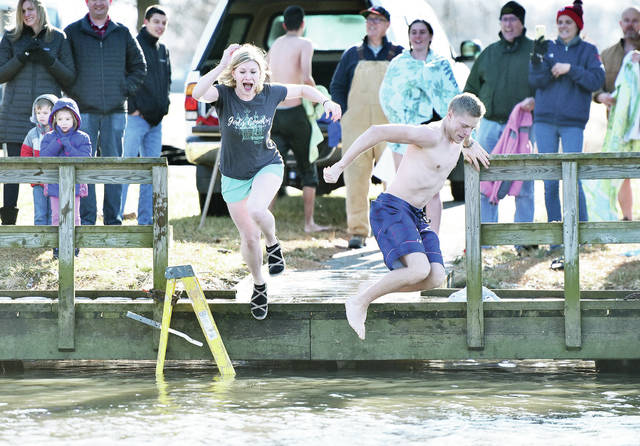 Claire Schmitmeyer, left, of Coldwater, and Jacob Kleinhenz, of Maria Stein, jump into Lake Loramie on new year's day. Fifteen people jumped into Lake Loramie on Wednesday, Jan. 1, as part of an annual tradition started by the Rev. Ethan Moore. He organized the annual jump to dedicate the new year to Jesus through his mother, Mary, on her feast day. Due to recent warm weather there was no ice on the lake that needed to be cut through for the jump. The jump occurred at around 12:45 p.m. with the temperature hovering around 40 degrees. Some of the jumpers were warm enough to stand around and talk outside of their cars after the jump.