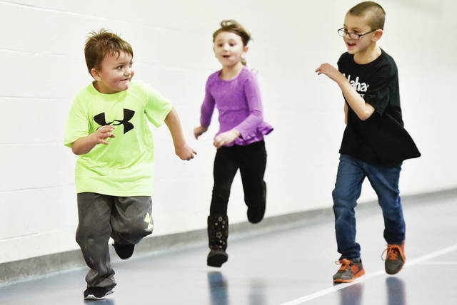 Colten Cornett, left to right, 5, son of Briana Cornett and Dillion Cornett, runs from Evelyn Dunn, 5, daughter of Billie Webb and Jim Dunn, and Braden Ernst, 7, all of Sidney, son of Katie Ernst, during a game of Dead Ant at the Sidney-Shelby County YMCA on Friday, Jan. 3. The kids are in the YMCA School Age Program.