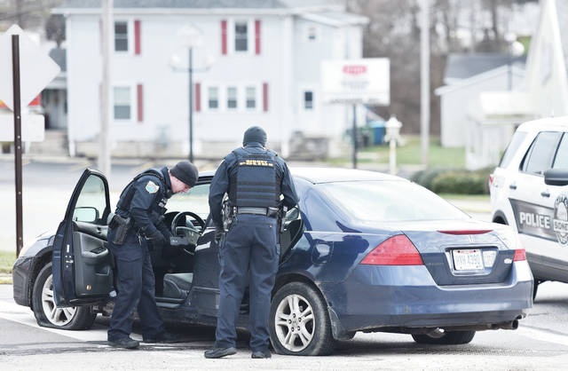 Sidney police search a car after it was involved in a chase in Sidney on Sunday, Jan. 5. Law enforcement attempted to stop the car in Sidney after it was reported stolen. The male driver refused to stop leading area on a chase around Sidney. The chase came to an end at the intersection of Kossuth Street and Wapakoneta Avenue after the cars tires were flattened with stop sticks at around 3:15 p.m..