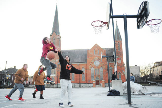 Ty Young, flies towards the net as Caden Herron, far right, 15, both of Sidney, son of Nicole Herron, defends during a game of two on two basketball in the Holy Angels Catholic Church parking lot on Sunday, Jan. 5. Watching the play are Parker Young, far left, 16, son of Chad Campbell and Britney Young, and Jace Herron, 13, both of Sidney, son of Nicole Herron and Maurice Jones. The boys play basketball an average of four times a week. They shovel snow off the basketball court when needed at Stephen Brown Park.