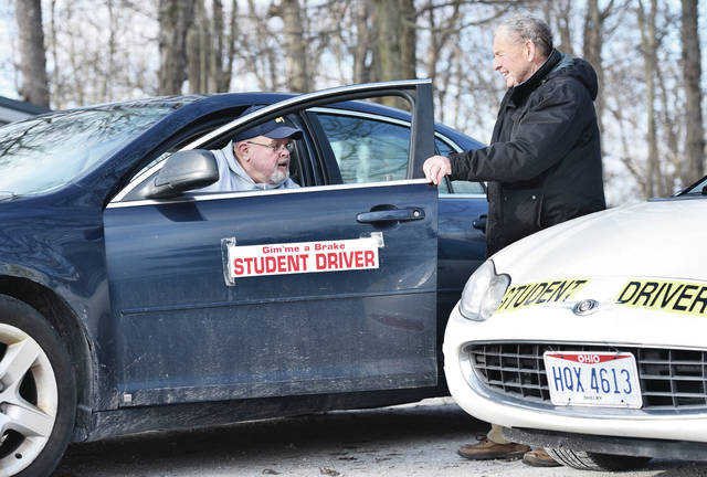 Dan Allen, left, of Maplewood, and Larry Allen, of Sidney, talk on Wednesday, Jan. 8, by the cars they used to help train student drivers through Allen's Driving School. After 43 years in business, Larry Allen closed the school in December.