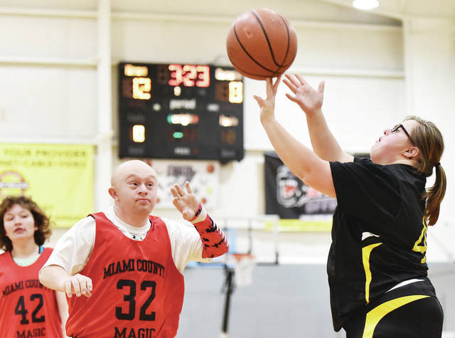 Shelby County Stingers' Mikayla Ryder shoots as Miami County Magic's Courtney Kroger, far left, and Cooper Brown defend. The Shelby County Special Olympics basketball game was held at Christian Academy Schools on Wednesday, Jan. 8.