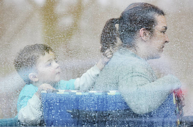 Viewed through a rain covered window of the Amos Memorial Library Jackson Shadley, left, 3, plays with the hair of his mom, Megan Shadley, both of Anna, on Friday, Jan. 10. Jackson is also the son of Todd Shadley.