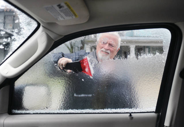 Dave Allspaw, of Sidney, scrapes ice from the window of his SUV parked on South Main Avenue Saturday, Jan. 18. Ice coated trees and roads Saturday morning as rain continued to fall.