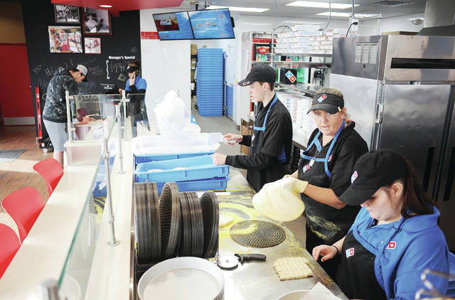 Kaden DeMarcus, left to right, orders a chicken, bacon and ranch pizza from Beth Amerine, both of Sidney, while Blake Kaminski, Michelle Runkle, both of Bellefontaine, and Tumairra Hoover, of Sidney, make pizzas and bread sticks at the new Domino's Pizza on Wednesday, Jan. 22. According to Amerine the restaurant has been very busy since opening this week. Kaminski and Runkle have been brought in temporarily to train new employees. The store is located at 1109 Wapakoneta Avenue.