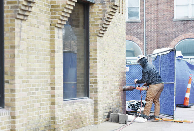 Jerriod Campbell, of Cincinnati, drills a hole through bricks covering the building at 101 S. Ohio Ave. on Friday, Jan. 24. Campbell has been drilling holes for out spouts, a sprinkler system and plumbing for what will be Tavolo Modern Italian.