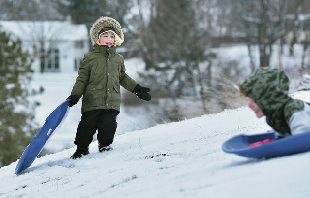 Morgan Tucker, left, 3, watches as his brother Lane Tucker, 5, both of Sidney, both children of Camille Tucker, sleds past him at the Moose Golf Course on Sunday, Jan. 26. The brothers took advantage of the fresh snow which started falling the previous day.