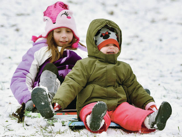 Adrienne Morrison, left, 8, daughter of Chelsea and George Morrison, and Gemma McMaken, 2, both of Sidney, daughter of Alyssa and Mitchel McMaken, sled down a hill at Tawawa Park on Sunday, Jan. 26. There was just enough snow for sledding earlier in the day before it started to melt.