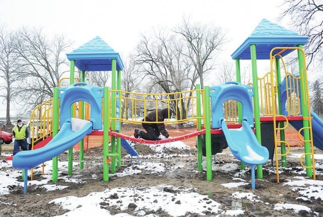 City of Sidney employee CJ Keener, of Sidney, pulls stickers off the bridge on the new playground equipment constructed at Roadside Park. The playground equipment was completed Monday, Jan. 27. The ground around the playground equipment is still very wet so the city will wait until it dries out or freezes before they clean it up. The jungle gym was built to replace an older one that was removed.