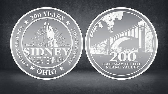 Shelby County and Sidney Bicentennial coins are shown in a display case. The protective cases, as well as limited quantities of the Sidney coins, remain available.