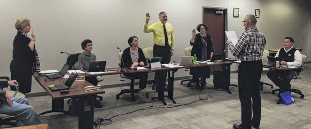 Sidney City Schools Treasurer Mike Watkins administers the oath of office to Michele Lott, left to right, Bob Smith and Mandi Croft during Monday night's board meeting.