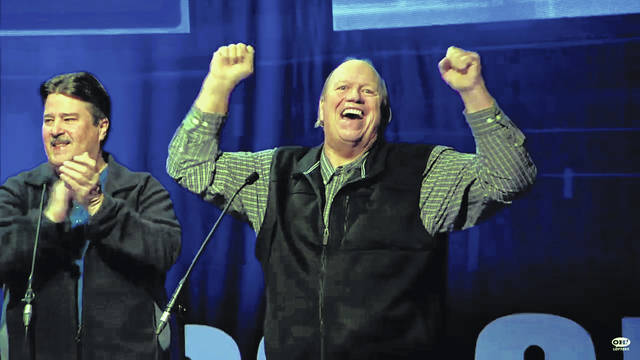 "Tedd Short, right, of Minster, reacts after winning Saturday's episode of ""Cash Explosion,"" an Ohio Lottery television show."