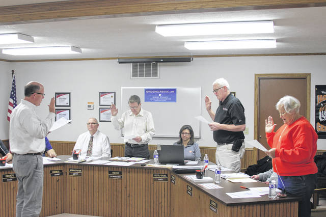 Jackson Center Village Solicitor Michael Burton administers the oath of office to Mayor Scott Klopfenstein and council members Ken Gloyeske and Karen Woodruff.