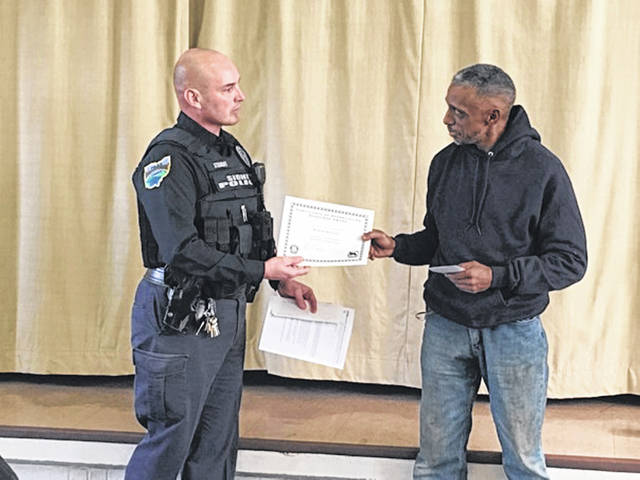 Officer Bryce Stewart, Sidney Police Department Community Resource officer presents the Sheepdog Award to Baron Brooks for alerting the city of damage done to a bridge.