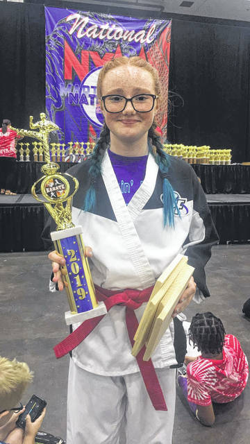Stari Williams-Smith poses with the first place trophy she earned for winning board breaking at nationals.