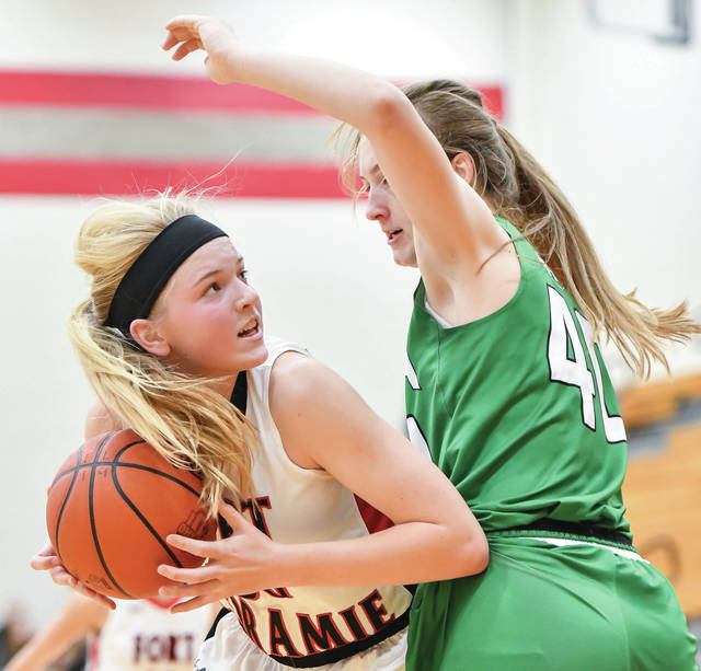 Fort Loramie junior forward Dana Rose looks to shoot with pressure from Anna's Lauren Barhorst during the second half of a Shelby County Athletic League game on Dec. 21 in Fort Loramie.