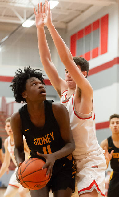 Sidney junior forward Avante Martin looks to shoot with pressure from Troy's Landyn Smith during the second half of a Miami Valley League game on Tuesday at the Trojan Activities Center in Troy. Martin led the Yellow Jackets with 17 points, 12 of which came in the second half.