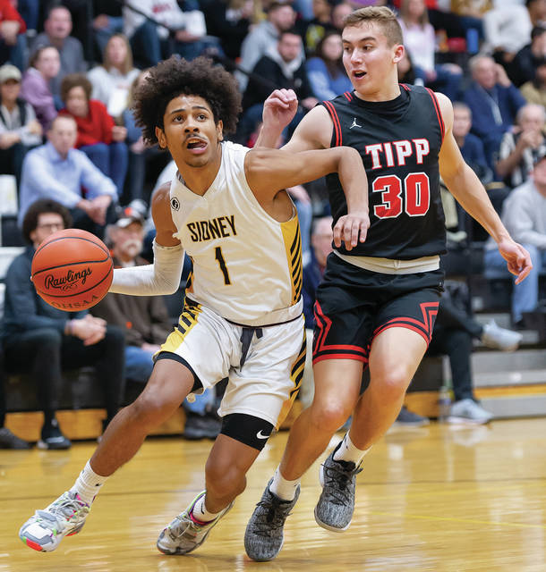 Sidney senior guard Dominick Durr dribbles with pressure from Tippecanoe's Griffin Caldwell during the first quarter of a Miami Valley League game on Tuesday in Sidney. Durr led the Yellow Jackets with 14 points and had three rebounds.