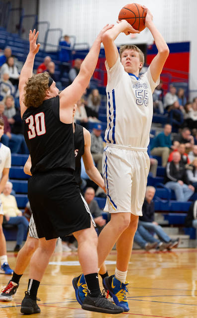 Lehman Catholic freshman post Justin Chapman shoots with pressure from Mississinawa Valley's Cody Dirksen during the first half of a Division IV sectional semifinal on Friday at Piqua's Garbry Gymnasium.