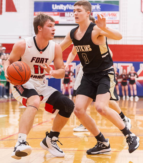 Fort Loramie senior guard Nick Brandewie dribbles with pressure from Botkins' Denton Homan during the first half of a Division IV district semifinal on Friday at Garbry Gymnasium in Piqua. The Redskins won 49-35 to secure their fifth consecutive district final berth.