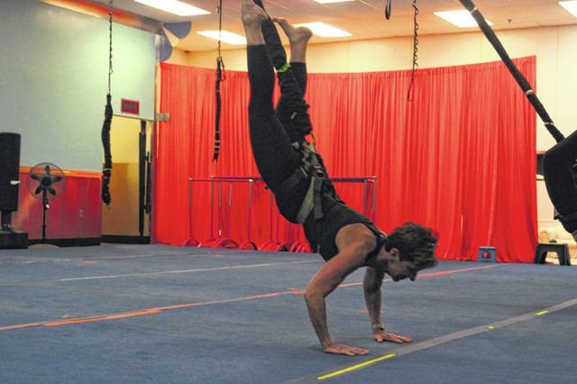 Kathy Wallace, co-owner of Heart and Sole Fitness, LLC, demonstrates a dive in a bungee workout. She and her daughter and co-owner, Chariti Moon, will hold a benefit on Saturday, Feb. 15, for a local family in need of a service dog.