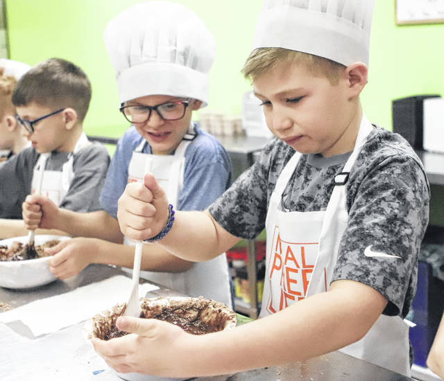 Lance Ward, 9, and Kaleb Ward, 7, sons of Jackie and Brandon Ward, of Sidney, and Kellon Schmiesing, 8, son of Tabitha and Nick Schmiesing, of Sidney, stir their brownie mix during a cooking class held at Meal Prep Life, 1544 Michigan St. Owners Julie and Joe Casiano held the cooking class and the young chefs prepared a meal of chicken enchilada bake, taco dip and brownies.